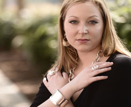 Image of attractive woman dressed in black wearing Blanca Flor sterling silver bracelet, rings, earings & necklace