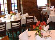 Image of fresh flowers, white tablecloths and original exposed brick in the front dining room of Chiapparelli's Restaurant Little Italy Baltimore MD