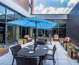 Image of Hyatt Place Hotel's enclosed open air patio with wooden flower boxes containing purple & yellow flowers, comfortable patio furniture with a bright blue umbrella and blue skies overhead, Harbor East Baltimore MD