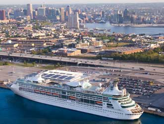 Image of Cruise Maryland Terminal next to I-95, with stately cruise ship in the foreground and Baltimore's Magnificent Inner Harbor in the background