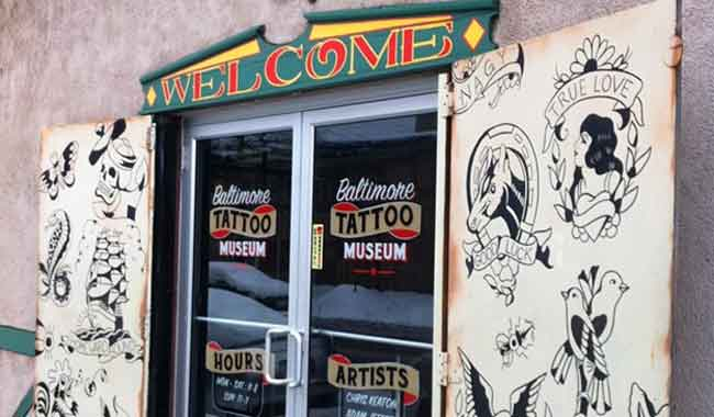 Photo of front entrance to Baltimore Tattoo Museum with artwork samples and colorful welcome sign, 1534 Eastern Avenue, Fell's Point, MD 21231