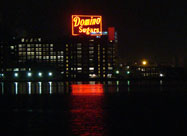 Night image of huge iconic red neon Domino Sugars sign, 120 feet by 70 feet, reflecting on the Patapsco River since 1951, taken from Harbor East looking at Locust Point, Baltimore, MD