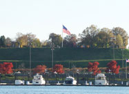 Image of Federal Hill Park in November viewed fron across the harbor with U.S. flags flying, colorful fall foliage & yachts in the foreground, Baltimore, MD