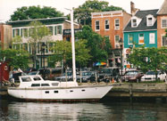 Serene image of white sialboat docked along historic old Belgian block Thames Street with its eclectic array of 18th century buildings that comprise the historic maritime community of Fell's Point, Baltimore, MD