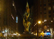 Glowing golden evening image of the Katyn Memorial framed by pretty holiday lights & tall buildings Harbor East, Baltimore, MD