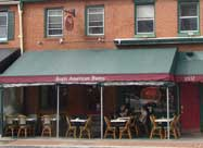 Image of Regi's American Bistro front sidewalk dining on the green and burgundy year-round heated outdoor patio on Light Street in historic Federal Hill Baltimore, MD