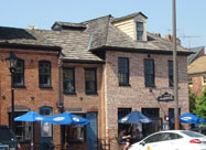 Image of waterfront dining outside the attractive historic brick building of the Point in Fells Restaurant on Belgian block Thames Street in Fell's Point, Baltimore, MD