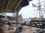 Awesome view of the harbor from the spacious second floor deck of Tir Na Nog Irish Bar & Grill showing the famous National Aquarium in Baltimore & the historic USS Constellation with its U.S. flag waving in the breeze at Harborplace, MD