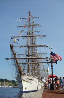 Image of visiting tall ship with colorful pennants flying in the mast docked at the Inner Harbor Promenade including a U.S. flag on the lamppost in the foreground for the Star-Spangled Sailabration in June 2012 Baltimore, MD